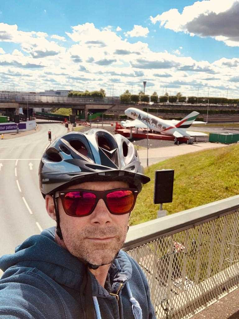 Chris cycling past Heathrow airport
